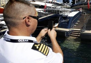 epa05560287 An officer takes a photo of one of the yachts being exhibited in the Monaco Yacht Show, moored up at Port Hercules, Monaco, 28 September 2016. The exhibition is one of the biggest European Yachting conventions and runs from 28 September until 01 October 2016.  EPA/SEBASTIEN NOGIER